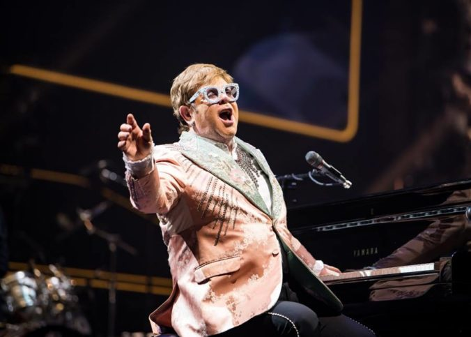 Elton John en concert jouant d'un piano